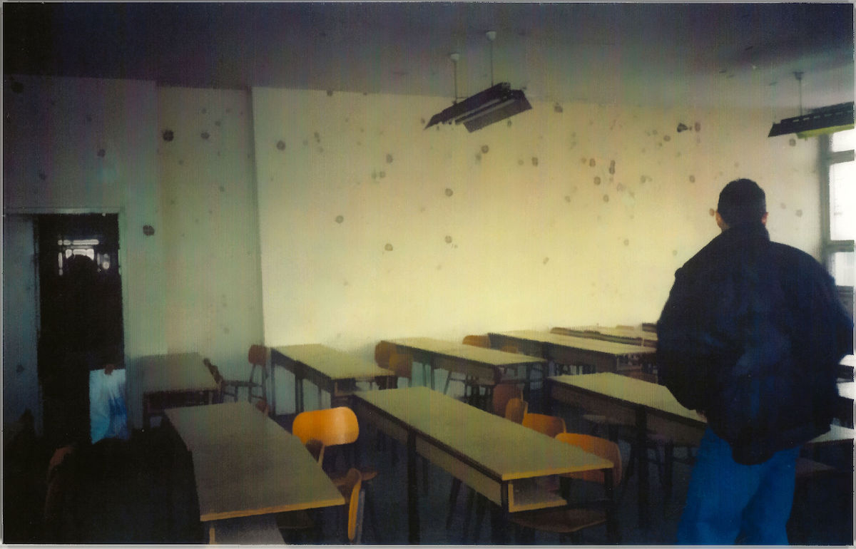 photo of an abandoned classroom with dozens of bullet holes in the wall